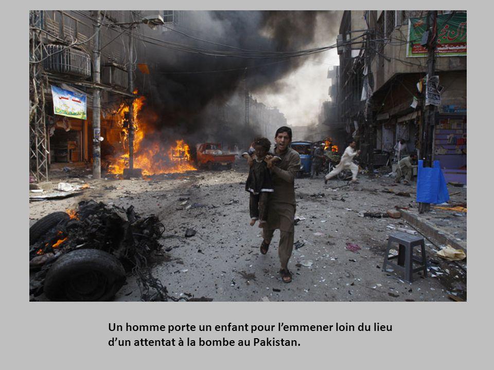 Un homme porte un enfant pour l'emmener loin du lieu d'un attentat à la bombe au Pakistan.
