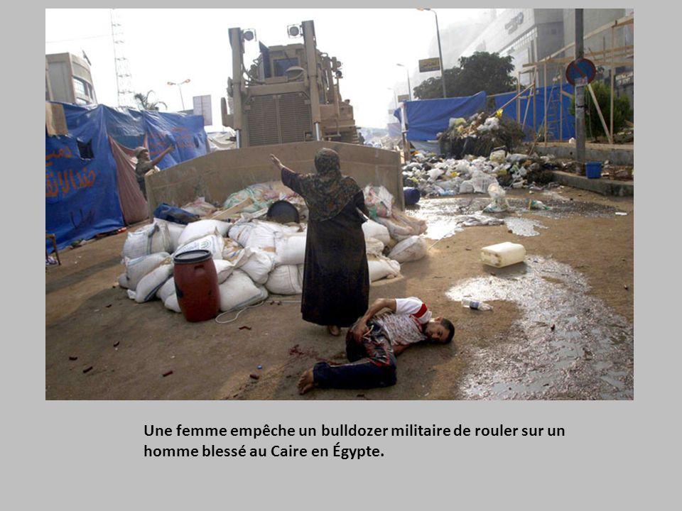 Une femme empêche un bulldozer militaire de rouler sur un homme blessé au Caire en Égypte.