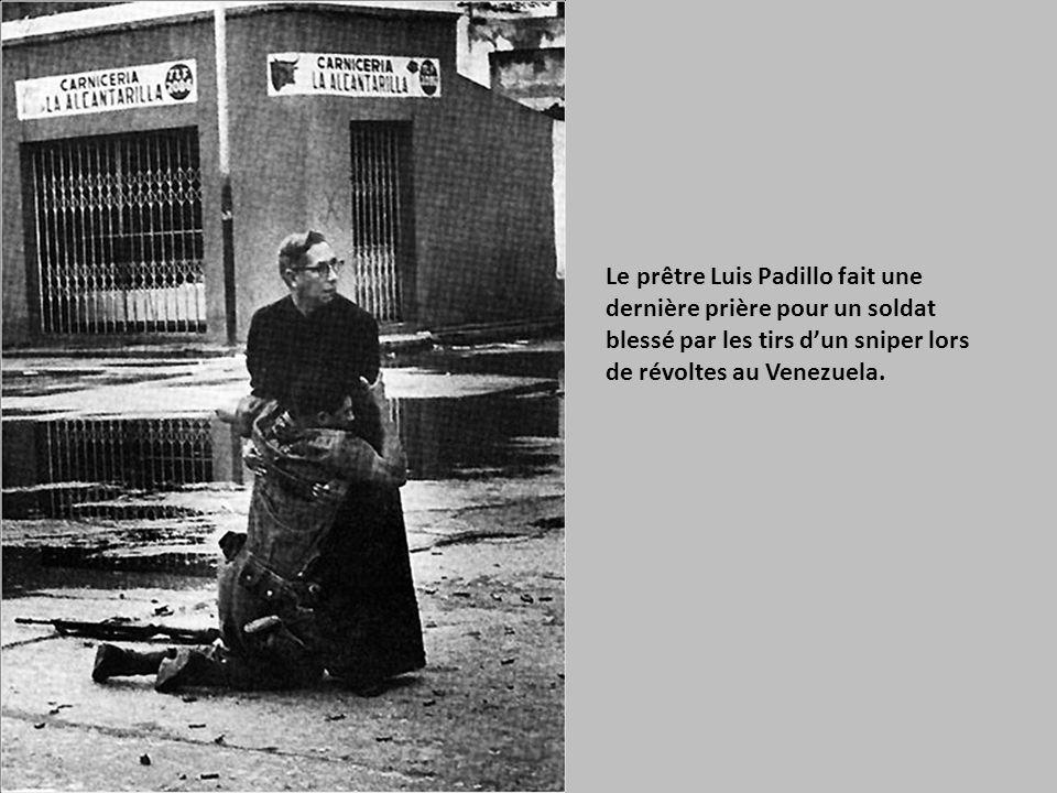 Le prêtre Luis Padillo fait une dernière prière pour un soldat blessé par les tirs d'un sniper lors de révoltes au Venezuela.