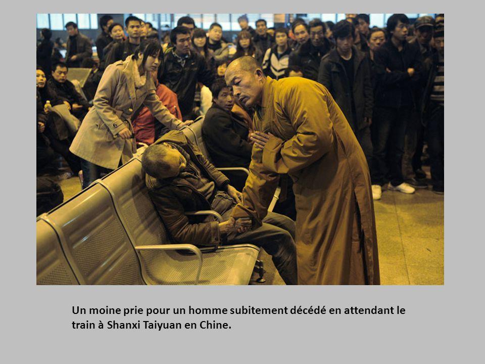 Un moine prie pour un homme subitement décédé en attendant le train à Shanxi Taiyuan en Chine.