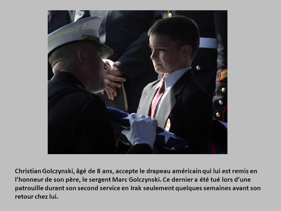 Christian Golczynski, âgé de 8 ans, accepte le drapeau américain qui lui est remis en l'honneur de son père, le sergent Marc Golczynski.