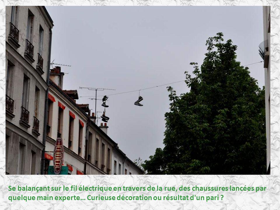 Se balançant sur le fil électrique en travers de la rue, des chaussures lancées par quelque main experte… Curieuse décoration ou résultat d un pari