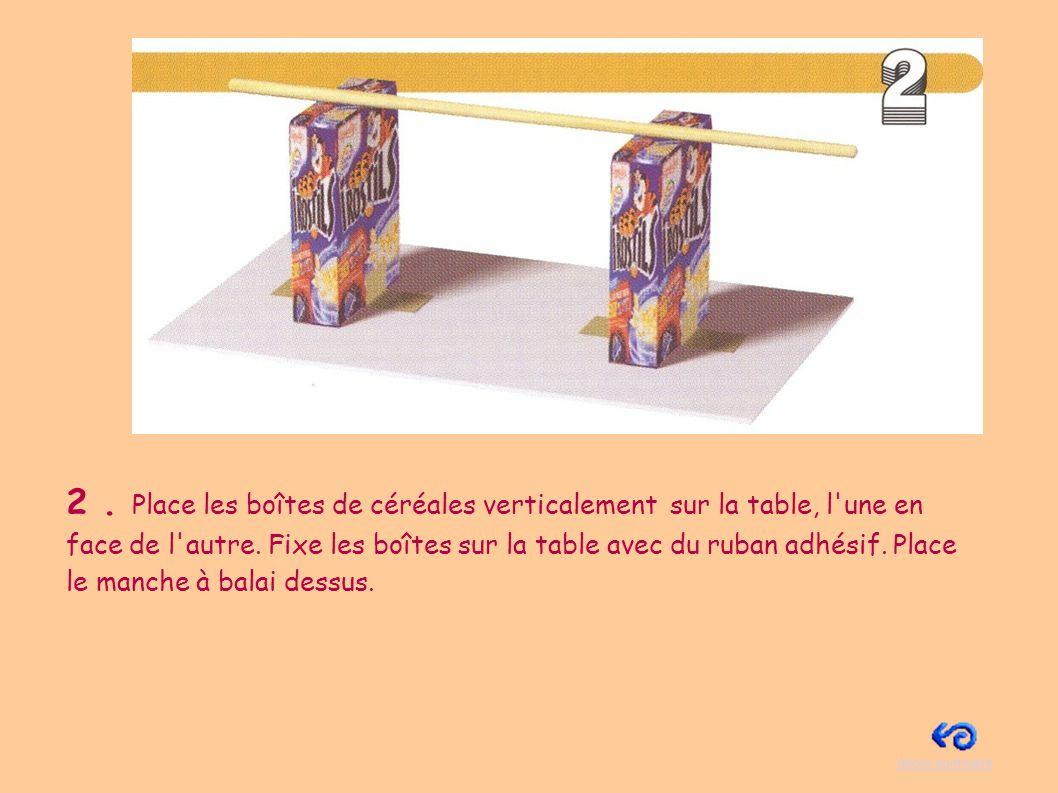 2 . Place les boîtes de céréales verticalement sur la table, l une en face de l autre. Fixe les boîtes sur la table avec du ruban adhésif. Place le manche à balai dessus.