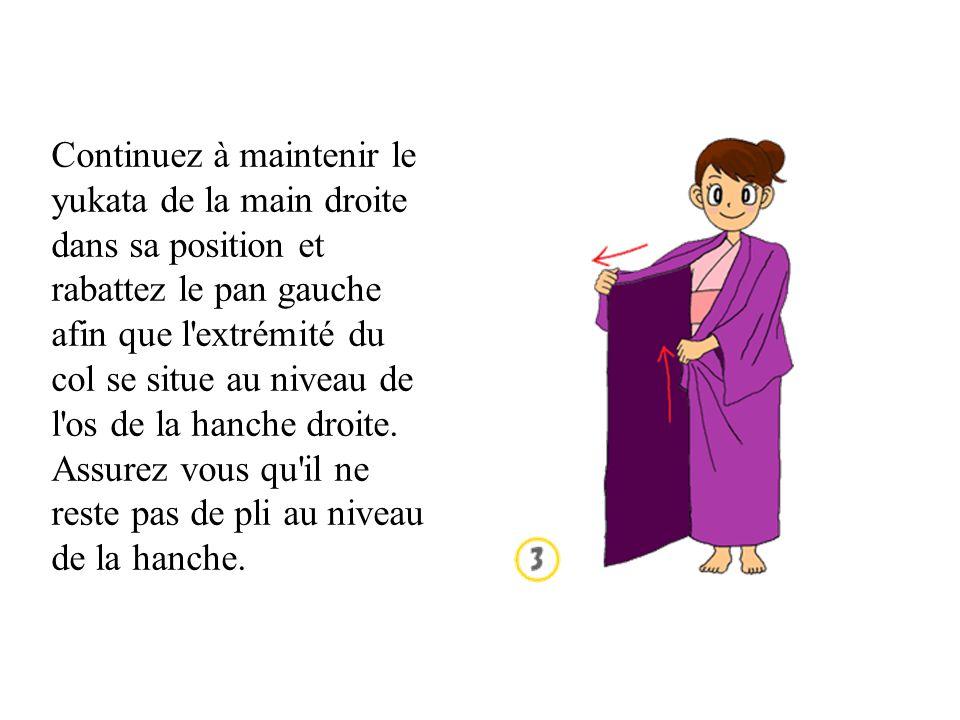 Continuez à maintenir le yukata de la main droite dans sa position et rabattez le pan gauche afin que l extrémité du col se situe au niveau de l os de la hanche droite.