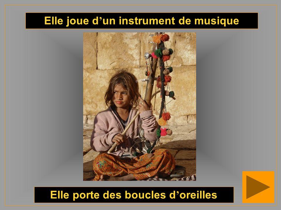 Elle joue d'un instrument de musique Elle porte des boucles d'oreilles