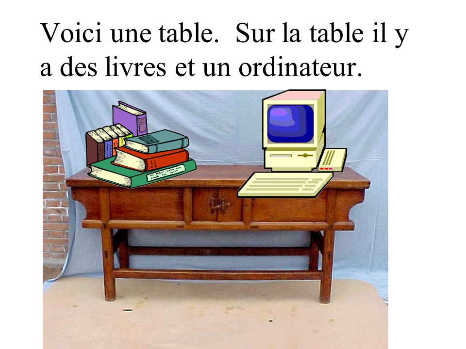 Voici une table. Sur la table il y a des livres et un ordinateur.