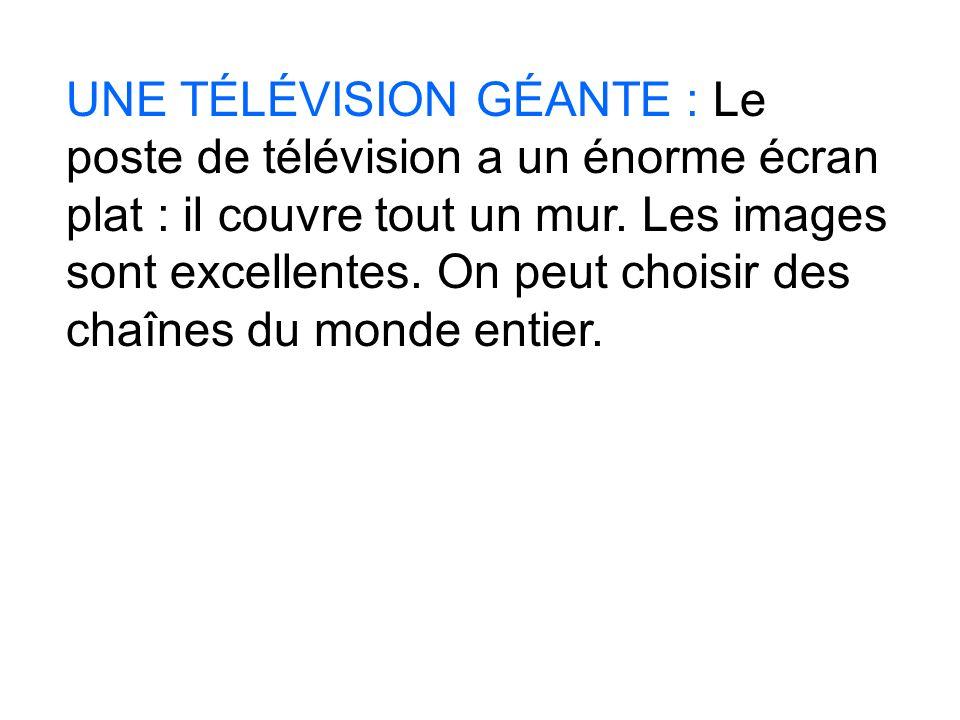 UNE TÉLÉVISION GÉANTE : Le poste de télévision a un énorme écran plat : il couvre tout un mur.