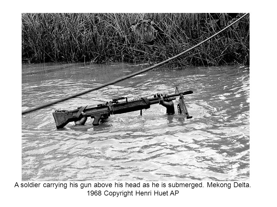 A soldier carrying his gun above his head as he is submerged
