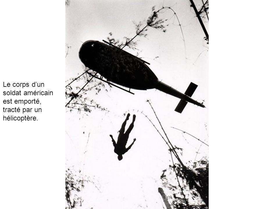 Le corps d'un soldat américain est emporté, tracté par un hélicoptère.