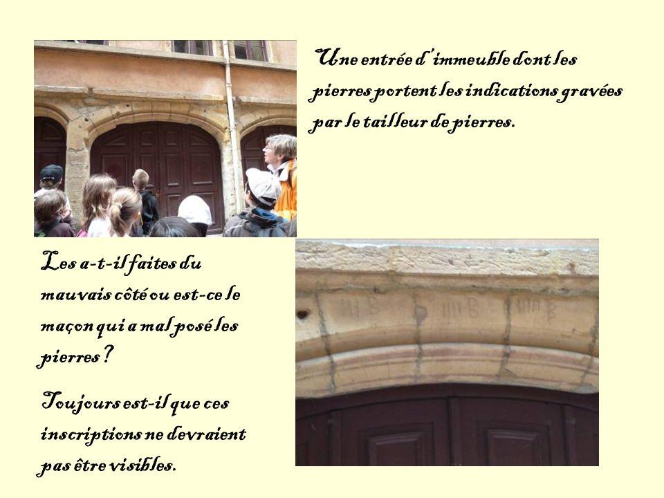 Une entrée d'immeuble dont les pierres portent les indications gravées par le tailleur de pierres.