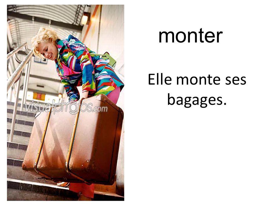 monter Elle monte ses bagages.