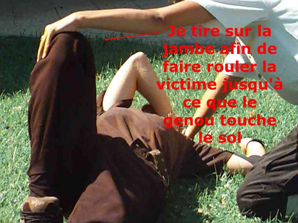 Je tire sur la jambe afin de faire rouler la victime jusqu à ce que le genou touche le sol
