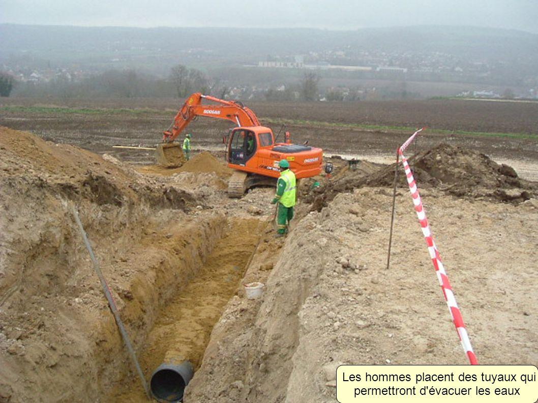 Les hommes placent des tuyaux qui permettront d évacuer les eaux