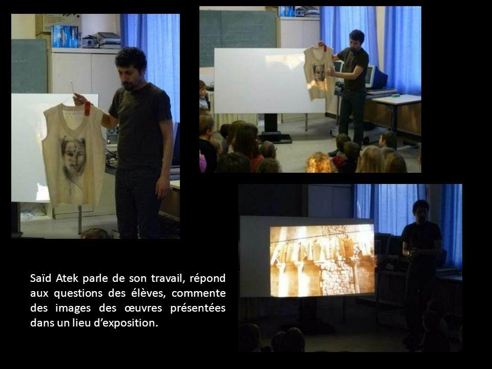 Saïd Atek parle de son travail, répond aux questions des élèves, commente des images des œuvres présentées dans un lieu d'exposition.